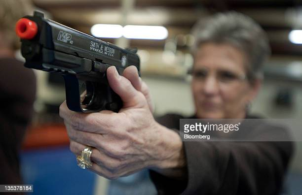 A student practices shooting a Smith Wesson Holdings Corp MP 40 Airsoft pistol during an all women class at the Oklahoma Personal Defense Academy in...