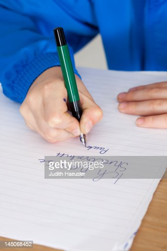 Student practicing handwriting in class : Stock Photo