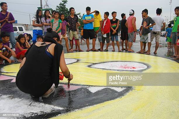 A student protester paints part of President Aquinos cartoon profile right on the street pavement of Commonwealth Avenue as a symbol of discontent on...