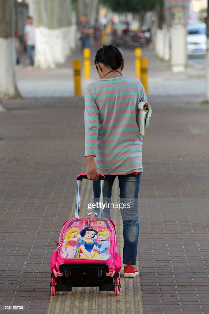 A student pulls her schoolbag for school on May 5, 2016 in Xiangyang, Hubei Province of China.