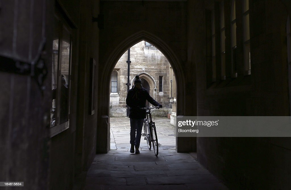 A student pushes a bicycle through an archway at Trinity College, part of the University of Cambridge, in Cambridge, U.K., on Friday, March 22, 2013. In 2011, the U.K.'s government unveiled a plan to reduce state spending on higher education and shift more of the costs to students through tuition increases and a loan program. Photographer: Chris Ratcliffe/Bloomberg via Getty Images