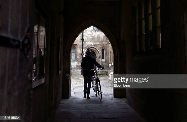 A student pushes a bicycle through an archway at Trinity College part of the University of Cambridge in Cambridge UK on Friday March 22 2013 In 2011...