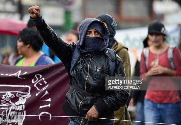 A student raises his fist as he takes part in a demonstration to commemorate the massacre of Tlatelolco in Mexico City on October 2 2014 Mexico...