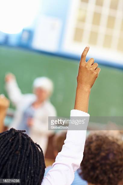 Student raising hand to answer the question