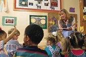 Student raising her hand as teacher reads a book