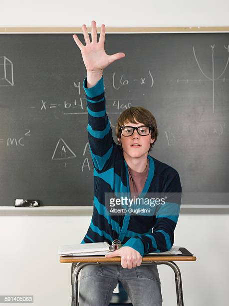 Student raising his hand at desk in classroom