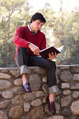 Student Reading Book and Sitting on Stone Wall