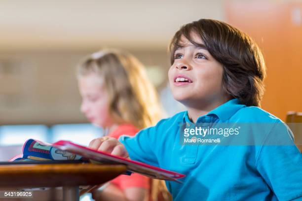 Student reading book at desk