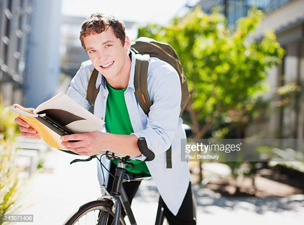 Studente lettura libro in bicicletta