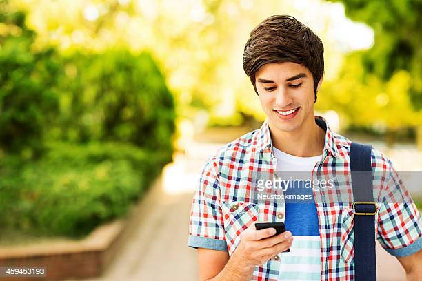 Student Reading Text Message On Smart Phone At Campus