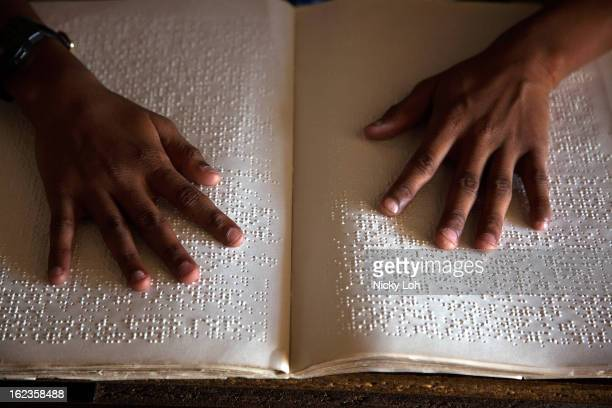A student reads Braille with her hands at the Government High School for The Blind on February 22 2013 in Kadapa India The school which is funded by...
