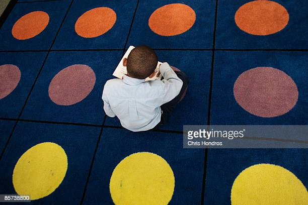 A student reads on a dotted carpet where students often sit for class at Harlem Success Academy a free public elementary charter school March 30 2009...