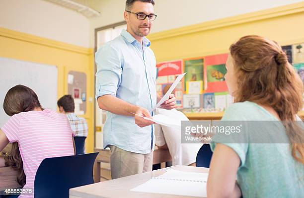 Student receiving exam paper from teacher