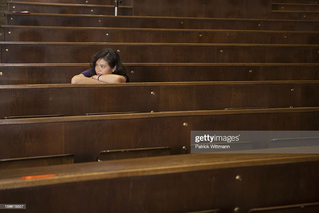 Student resting head on desk in class : Stock Photo