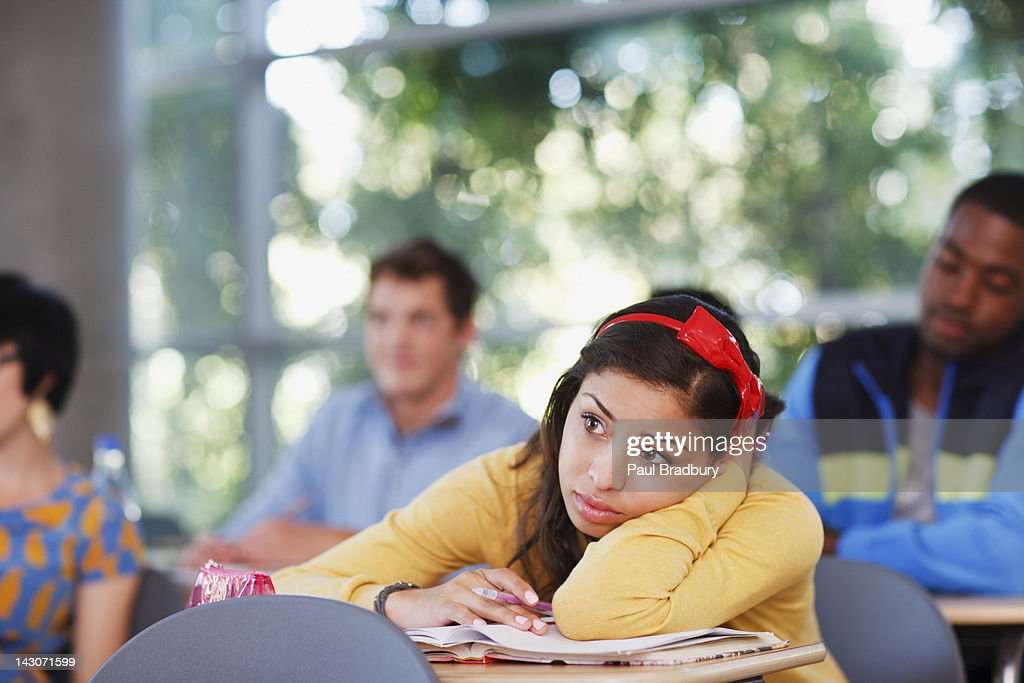 Student resting head on desk in classroom : Stock Photo