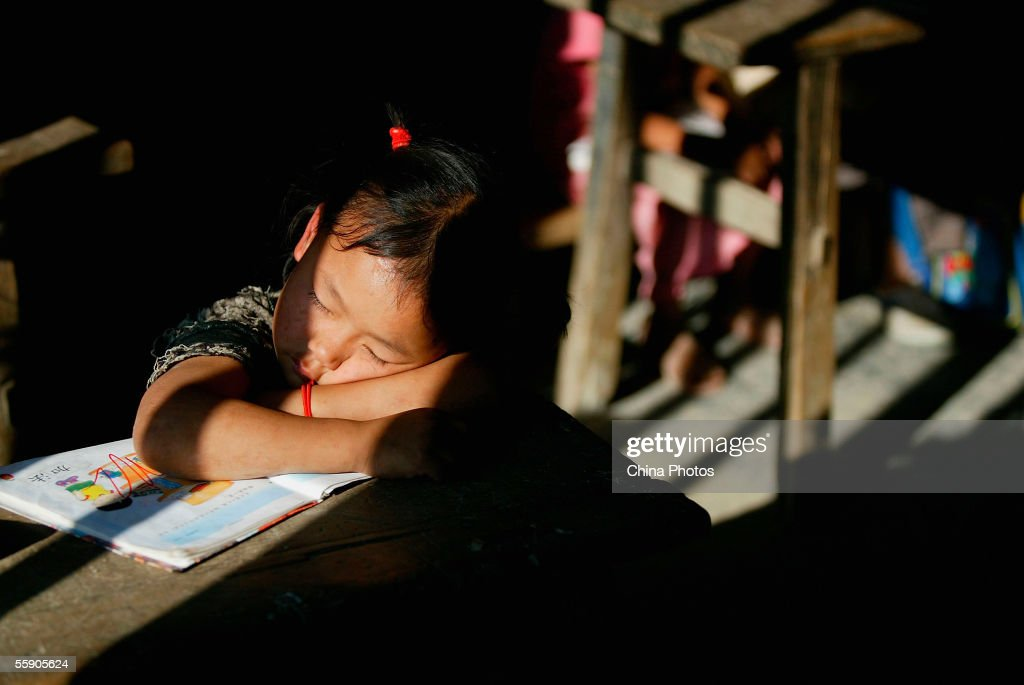 A student rests during class break at a shabby classroom under the sunlight in a country primary school on October 10, 2005 in Baise, a mountainous area of Guangxi Zhuang Autonomous Region, China. According to state media, many children in rural regions in China are facing school dropout because of poverty. Longstanding problems such as inadequate staffing, low pay and brain drain are also blocking education in China's rural areas, prompting government action to implement compulsory education.