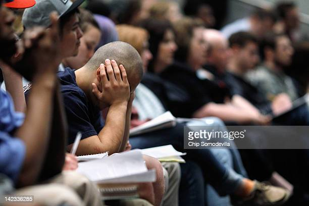 A student rests his head in his hands while listening to Republican Presidential candidate former House Speaker Newt Gingrich address a campaign town...