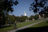 A student rides his bike across Dartmouth College campus the day before a Republican presidential debate sponsored by Bloomberg via Getty Images and...