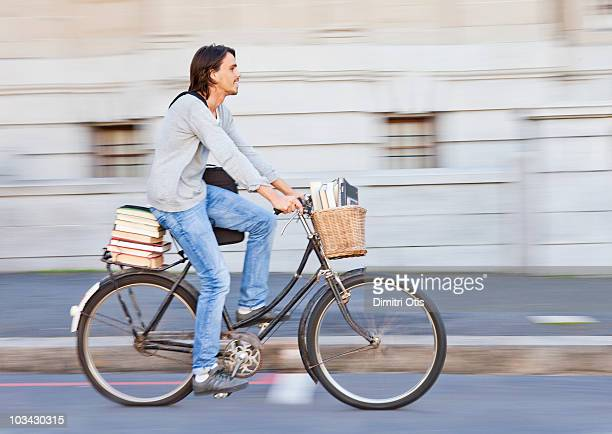 Student riding bicycle carrying many books