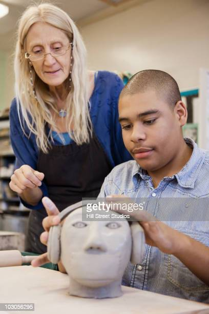 Student sculpting bust in classroom