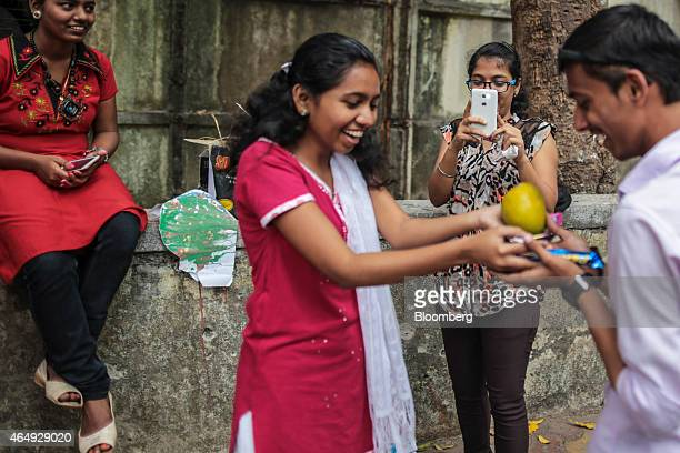 A student second right takes a photograph using a Micromax Informatics Ltd smartphone in Mumbai India on Saturday Feb 28 2015 The government auction...