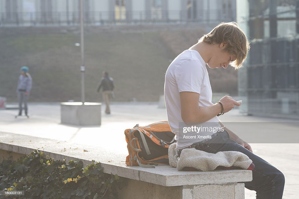 Student sends text from stone wall, skateboarder : Stock Photo