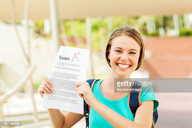 Student Showing Test Result With A+ Grade On University Campus