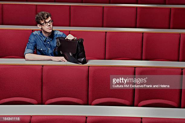 Student sitting in empty classroom