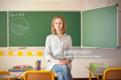 Student sitting on desk in classroom : Stock Photo