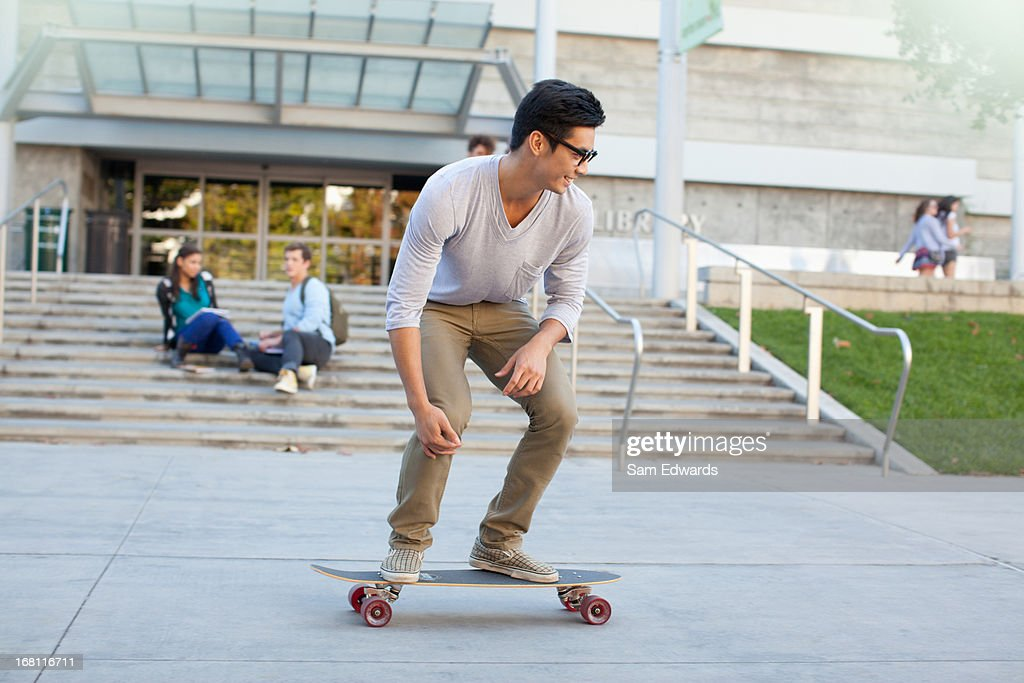 Student skateboarding on campus : Stock Photo