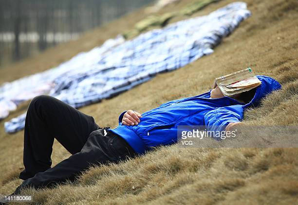 A student sleeps with a book covering his face as sheets laid on the ground are aired in the sun at Jiujiang University on March 12 2012 in Jiujiang...