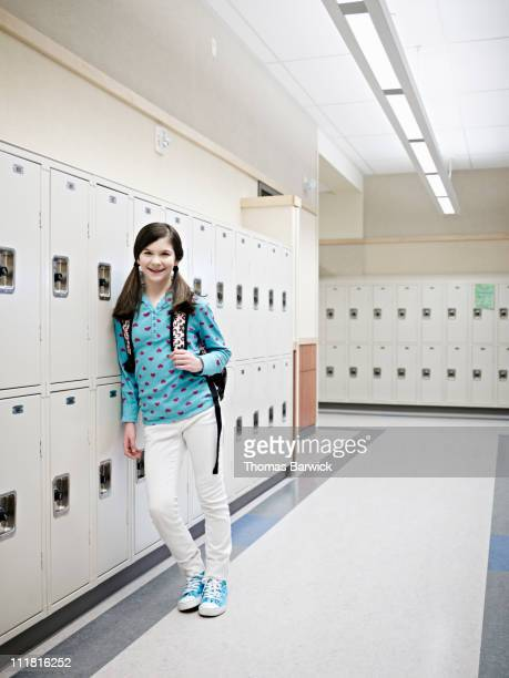 Student smiling leaning against school lockers