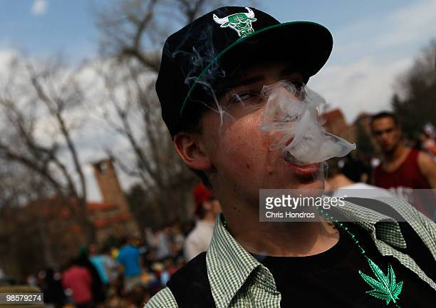 A student smokes a marijuana cigarette during a 'smoke out' with thousands of others April 20 2010 at the University of Colorado in Boulder Colorado...