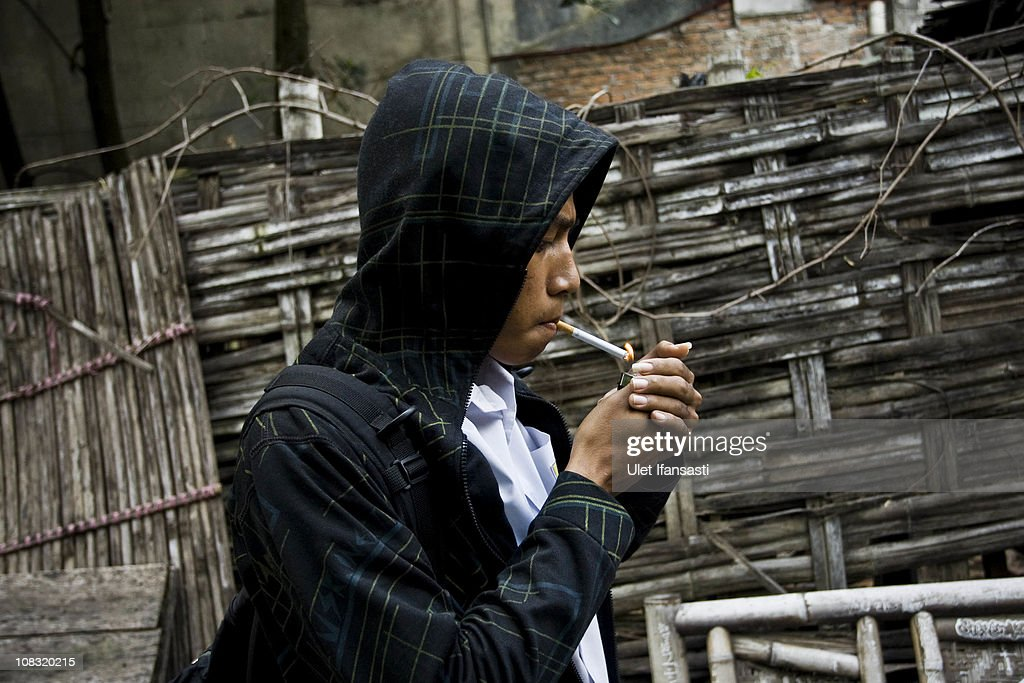 A student smokes after school on January 25, 2011 in Yogyakarta, Indonesia. It is estimated that over 25 percent of children in Indonesia over the age of three have tried smoking, with over three percent of them smoking regularly. The lack of government regulation around advertising is blamed for the problem, with campaigns seen heavily at sporting events, music concerts. The Indonesian government previously passed a health bill in 2009 to address the issues, but it has not yet been implemented.