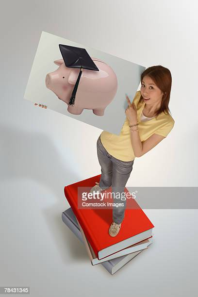 Student standing on books and holding photo of piggy bank