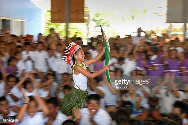 A student stands out from the crowd as she races through her school carrying the Melbourne 2006 Queen's Baton during the Nauru leg of the baton's...