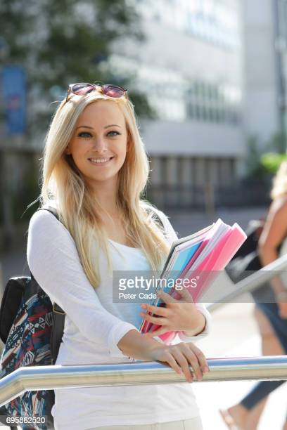 Student stood outside holding work