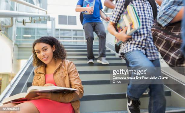 Student studying on busy stairs