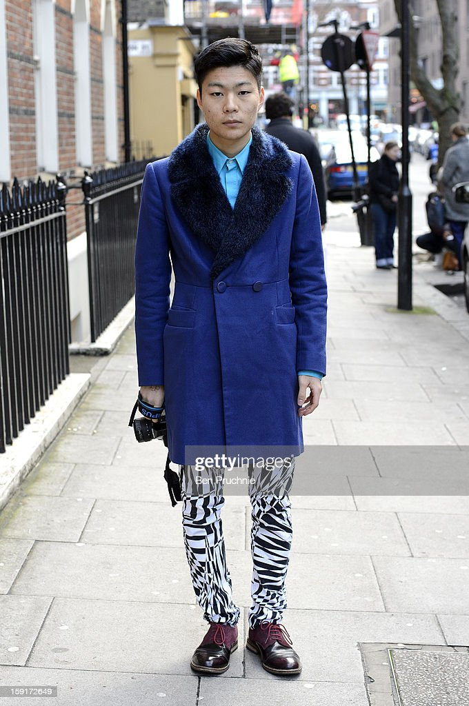 Student Taka (19) poses wearing a French Connection coat, H+M shirt and trousers with vintage shoes at the Shaun Samson catwalk presentation during London Collection: MEN on January 9, 2013 in London, England.