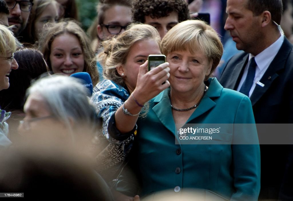 A student takes a picture with her cell phone of her together with German Chancellor Angela Merkel as she arrives for a visit to the Heinrich Schliemann Gymnasium in Berlin, Germany on August 13, 2013. German Chancellor Angela Merkel, campaigning for a third term, filled in as a school history teacher on August 13, 2013 , the anniversary of the building of the Berlin Wall.