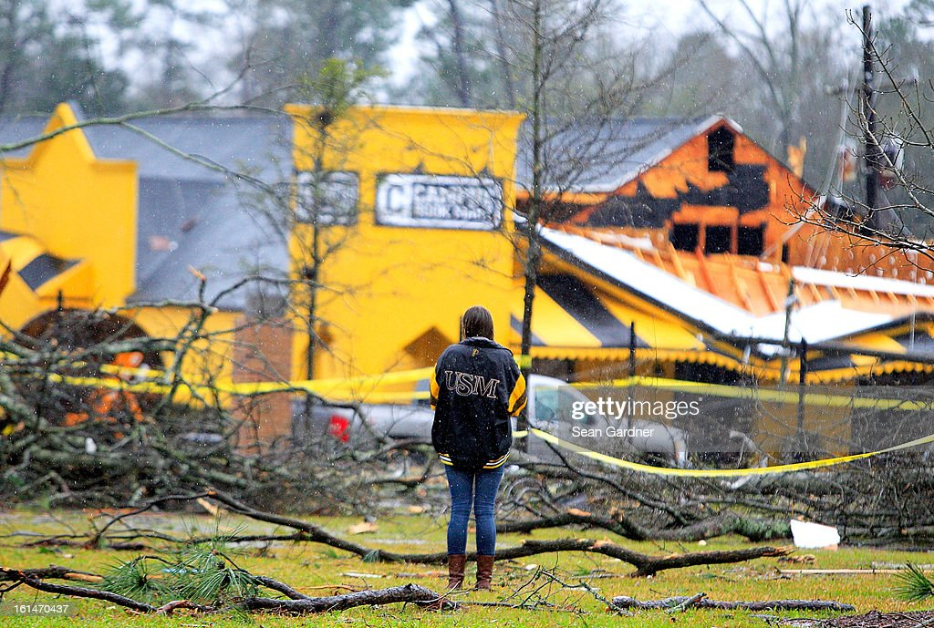 A student takes a picture with her iphone on the campus of the University of Southern Mississippi after a tornado touched down yesterday evening on February 11, 2013 in Hattiesburg, Mississippi. Hundreds of homes were destroyed and over sixty people injured when the tornado ripped through the town.