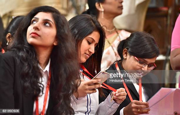 A student takes the photo of her gold medal during the procession of the 160th annual Convocation of Mumbai University at Cowasji Jehangir Hall on...