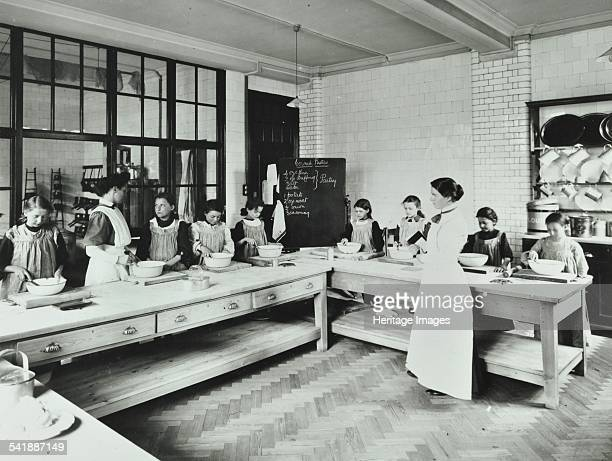 Student teacher in a cookery lesson Battersea Polytechnic London 1907 Taking a cookery lesson for children but under supervision Artist unknown