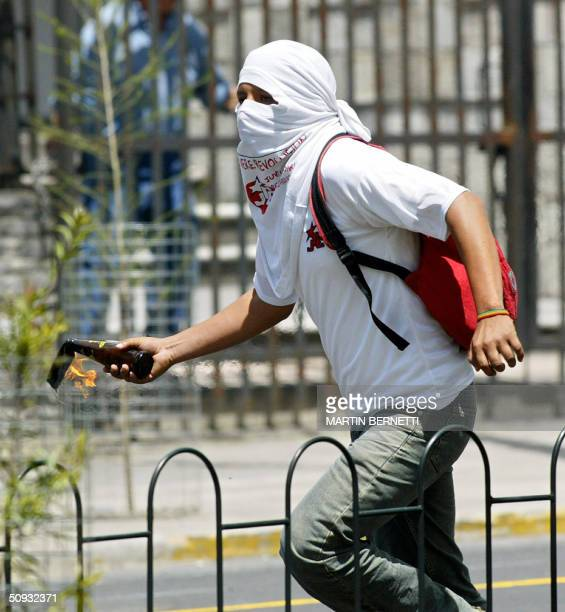 A student throws an incendiary bomb at antiriot policemen during a demonstration against the 34th General Assembly of the Organization of American...