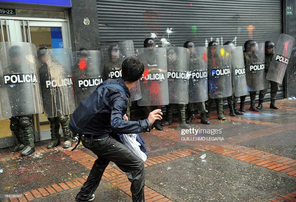A student throws paint bombs against riot police during a protest in Bogota, Colombia on March 21, 2013, demanding a better and free education and an alternative university reform. AFP PHOTO/Guillermo Legaria