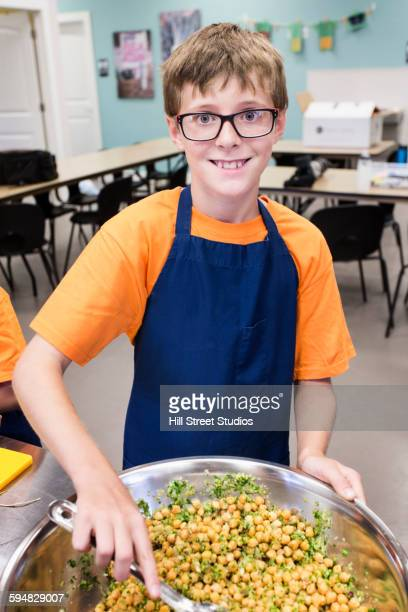 Student tossing salad in cooking class