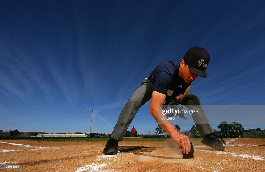 A student Umpire cleans home plate before participationg in a simulated baseball game during the Jim Evans Academy of Professional Umpiring on January 27, 2011 at the Houston Astros Spring Training Complex in Kissimmee, Florida. Jim Evans was a Major League Umpire for 28 years that included umpiring four World Series. Many of his students have gone on to work on all levels of baseball including the Major Leagues.