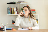 Student having an asthma attack using an asthma inhaler at home