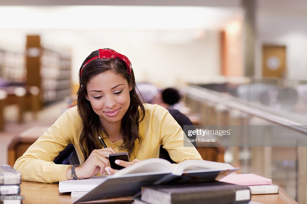 Student using cell phone and studying in library : Stock Photo