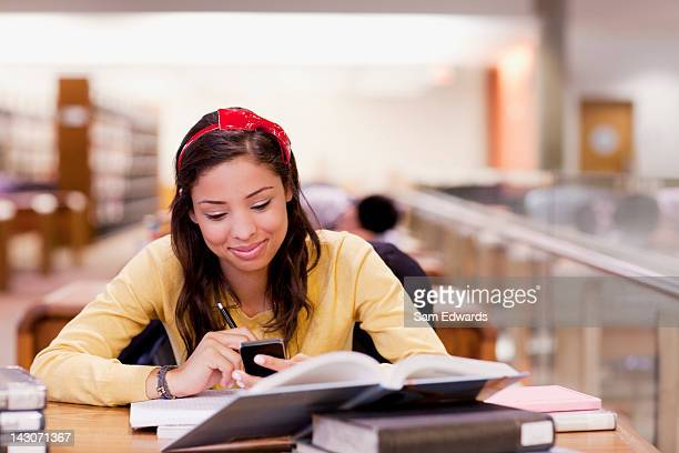 Student using cell phone and studying in library